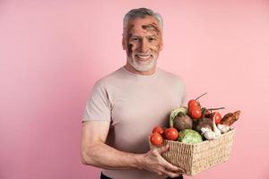 Older man keeps useful with home-grown products grown on organic soil photo
