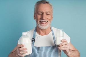 lindo abuelo con cabello gris y barba sostiene una botella de leche foto