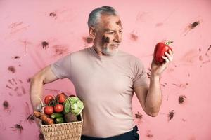 Attractive, older man holds a basket of vegetables photo