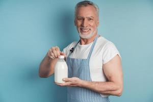 hombre sonriente sosteniendo una botella de leche foto