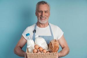 A senior man holding a basket with food bread, milk, eggs photo