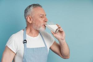 Vista lateral, hombre mayor bebiendo leche, cerrando los ojos foto