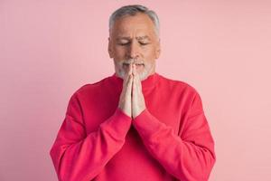 Man with closed eyes meditates on a pink background photo