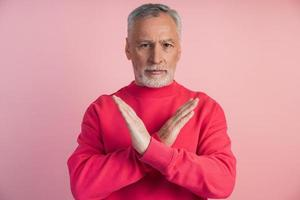 Senior man gesturing on pink background photo