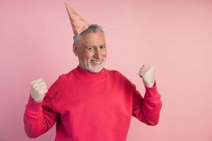 Hombre mayor seguro en un sombrero de fiesta se regocija en la victoria foto
