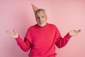 Senior man with a festive hat on a pink background photo