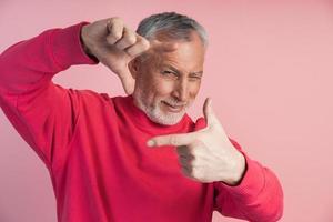 hombre de barba gris hace un marco con sus dedos, foto