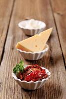 tomates secados al sol y dos tipos de queso foto