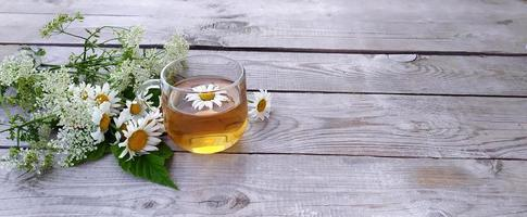 Chamomile aromatic tea in a glass cup on a wooden background photo