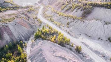 camino de ripio polvoriento a la cantera de piedra caliza con maquinaria pesada. foto