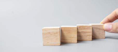 hand placing or pulling wooden block photo