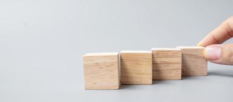 mano colocando o tirando de un bloque de madera foto