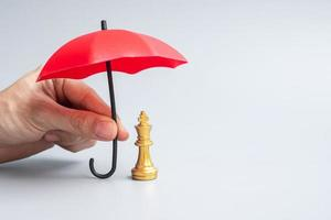 hand holding red Umbrella cover Chess King figure photo