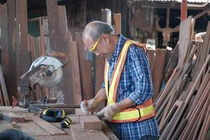 Carpintero senior masculino trabaja en la fábrica de madera. foto