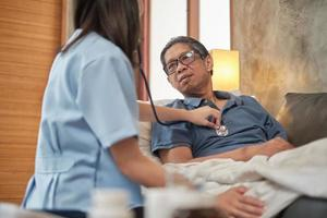 Doctora comprobando la salud del paciente masculino anciano asiático en casa. foto