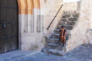 Mujer sentada en las escaleras de una iglesia medieval foto