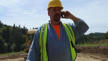 Blue collar worker walking and talking on phone video