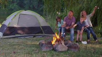 Family toasting marshmallows on camp fire video
