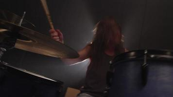 Man playing drums in heavy metal rock band, slow motion video