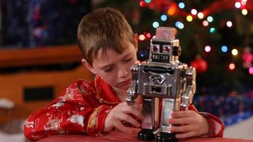 Boy playing with toy robot on Christmas video