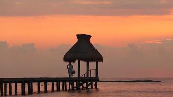 femme marche le long du quai pendant le coucher du soleil à tropical resort video