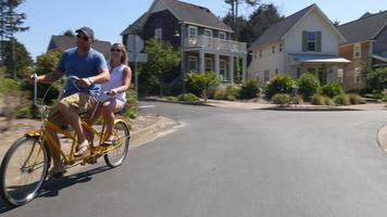 Couple riding tandem dans la communauté de vacances côtières video