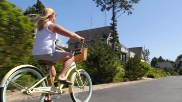 Woman riding bicycle dans la communauté de vacances côtières video