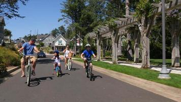 Famille faisant du vélo ensemble dans la communauté de vacances côtières video