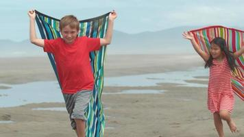 Kids running with towels at beach, slow motion video
