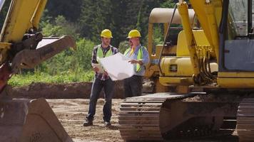 Two workers by excavation equipment look at blueprints video