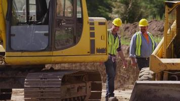 Two workers walking by machinery video