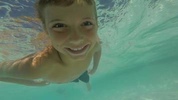 Young boy swimming in pool underwater, POV video