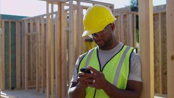 Construction worker texting on cell phone video