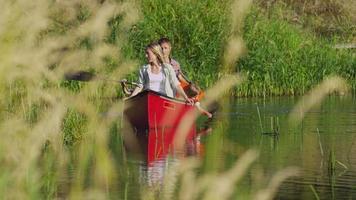 Family paddling canoe on lake video