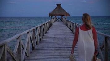une femme descend la jetée du tropical resort video