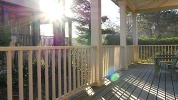 solljuset lyser genom räcken på strandhusets veranda video