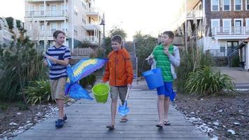 Boys walking along path to beach video