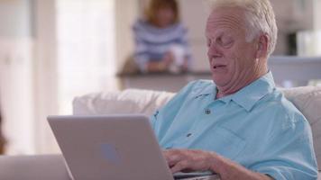 Senior man in living room using laptop computer video
