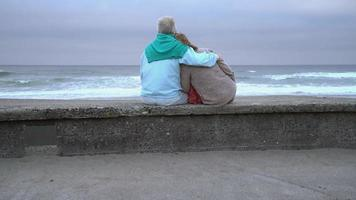 Senior couple sitting on wall at beach together video