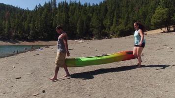 casal carrega caiaque para o lago video