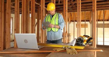 Trabajador de la construcción con tableta digital y computadora portátil video