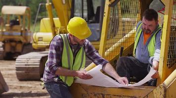 Excavators looking over plans video