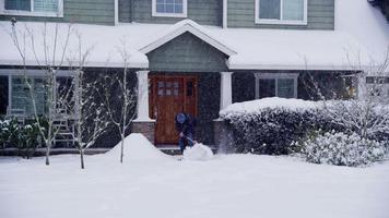 homme pelletant la neige devant la maison video