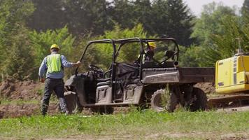 Workers get out of utility vehicle and walk to jobsite video
