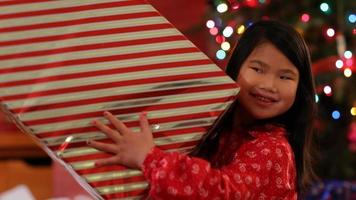 Portrait of young girl with large Christmas gift video