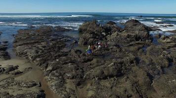 Aerial shot of family on rocks looking in tide pools video