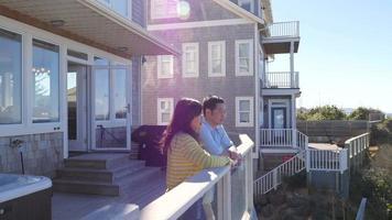 casal olha da varanda para a vista do mar video