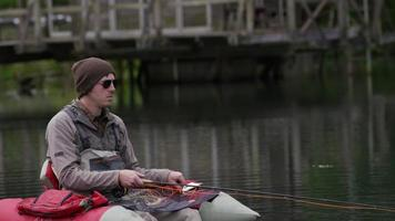 pescador com mosca pescando em tubo flutuante video