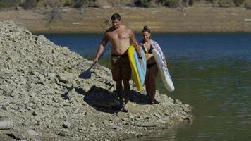 Pareja caminando por el lago con tablas de paddle surf video