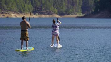 pareja, en, stand up paddle, tablas, en, lago video